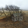 Abandonded farm house on a foggy day.