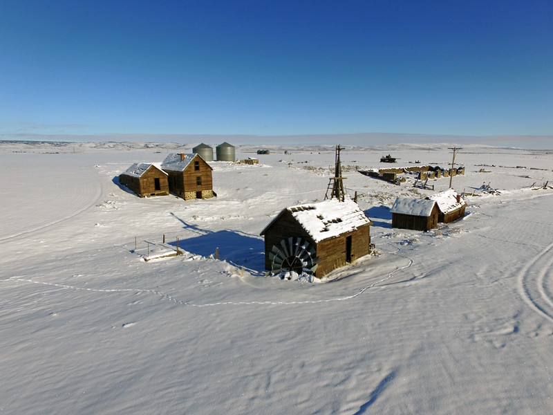 Abandoned farmhouse and windmill in winter.