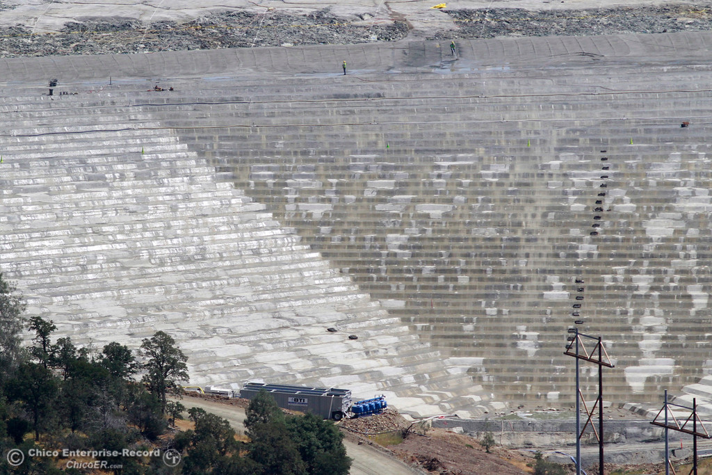 . Workers water down the emergency spillway splash pad. An aerial view of the Oroville Dam and spillway from the Butte County Sheriff\'s Office helicopter Friday, May 17, 2018, in Oroville, California. (Dan Reidel -- Enterprise-Record)
