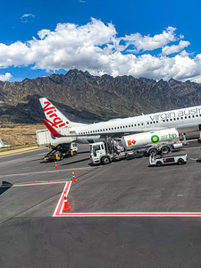 Southern Alps, Ka tiritiri o te Moana surrounding Queenstown New Zealand Airport with a Virgin Australia aircraft on the tarmac. Editorial photo
