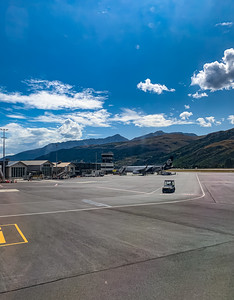 Southern Alps, Ka tiritiri o te Moana surrounding Queenstown New Zealand Airport with an aircraft on the tarmac. Editorial photo