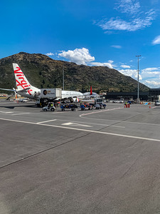 Southern Alps, Ka tiritiri o te Moana, surrounding Queenstown New Zealand Airport with a Virgin Australia aircraft on the tarmac. Editorial photo