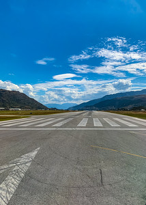 Southern Alps, Ka tiritiri o te Moana surrounding Queenstown New Zealand Airport with a runway, tarmac.