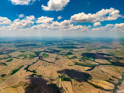 Aerial view of farmlands late spring, some with young crops on a beautiful white blue sky day.