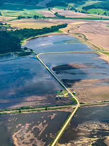 Aerial view of flooded farmlands late spring, some with young crops
