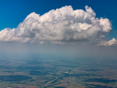 Aerial view of white cloud over rural farmland .