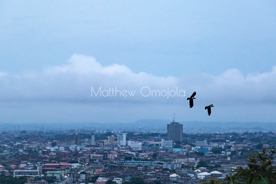 Aerial View Ibadan Nigeria on a Foggy day with two birds in the air. Cocoa House is the tallest building in the distance; the first skyscraper in Nigeria