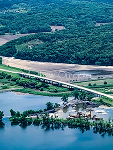 Aerial view of a bridge or overpass with flooded plains and quarry in the foreground.