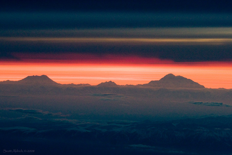 Mount Foraker (17,400'), Mt. Hunter (14,573') and Denali (20,320') poke above the clouds. Taken on descent into Anchorage.