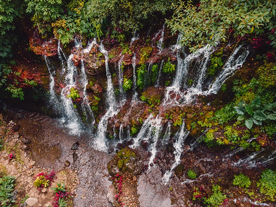 Amazing waterfall with clear water and red stones in tropical forest. Bali, Indonesia. Aerial view