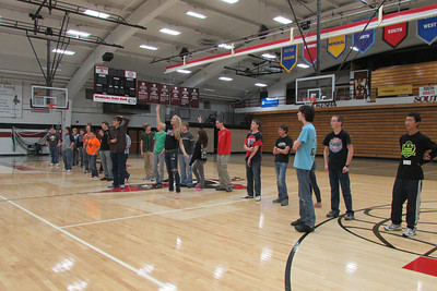 People line up to be choses for teams for Ultimate Frisbee in the gym