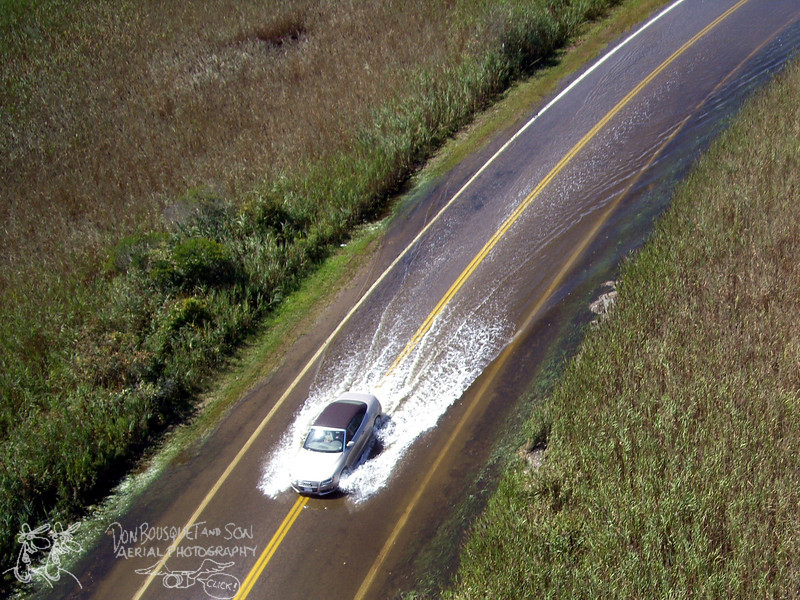 A car driving through the flooded causeway after Irene.