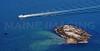 A fishing boat passes a small island in the Salem Sound.  Salem, Massachusetts.