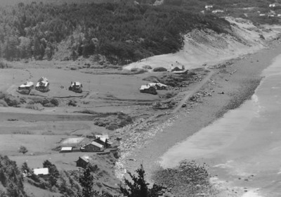 Taken early 1930s by Brubaker aerial studios. Sand now covers rocks on the beach so visible in the 1902 photo (first in this series). Jetties built at the end of the spit between 1912 and 1918 caused sand to accrete on the beach.