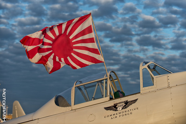 The war flag of the Imperial Japanese Army catches the wind above this Mitsubishi A6M Zero.