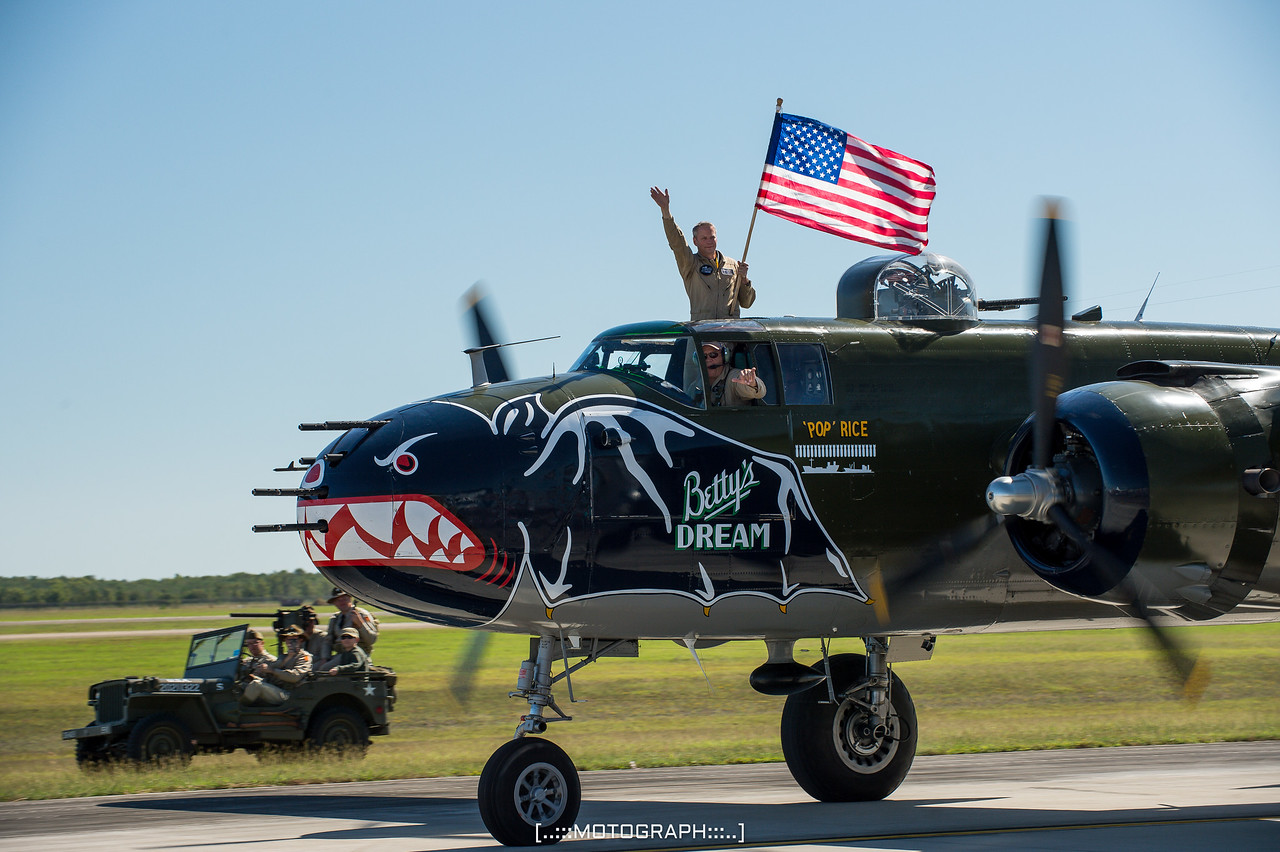 """The B-25J Mitchell """"Betty's Dream"""" taxies back after another successful flight.  WWII re-enactors are seen in the background in their iconic US Willy's Jeep."""