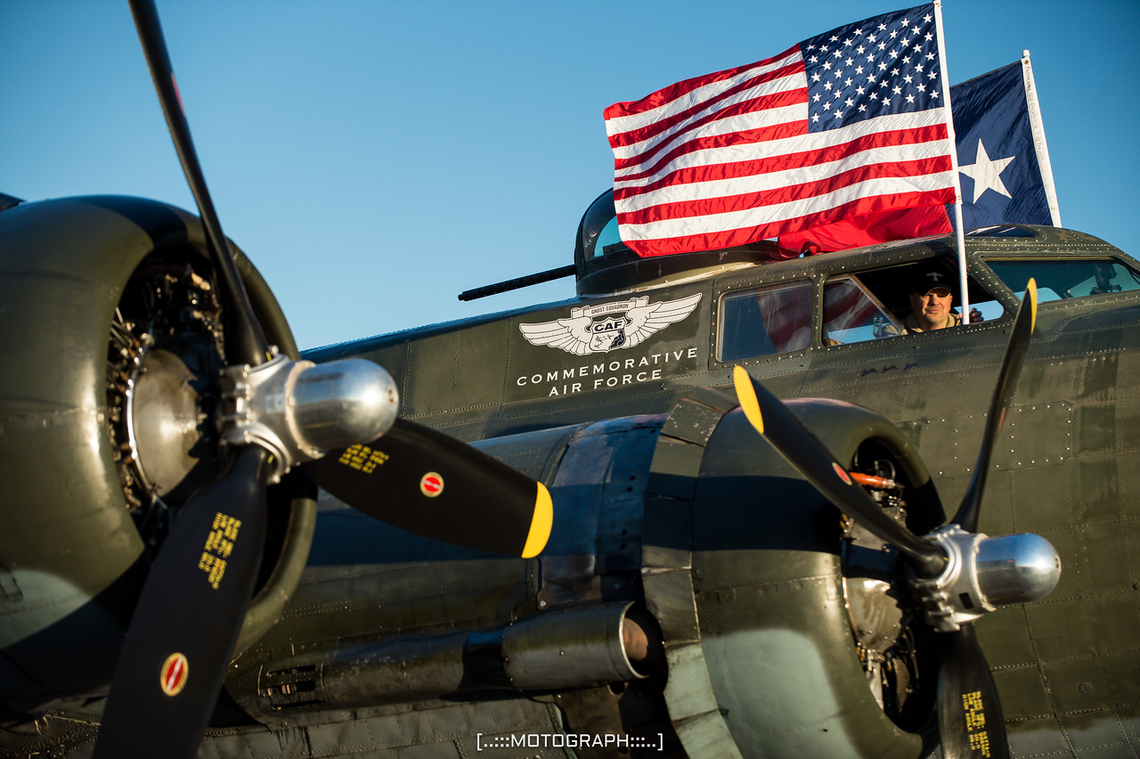 """Flags fly as the flight crew prepare the B-17 Flying Fortress """"Texas Raiders"""" for its performance"""