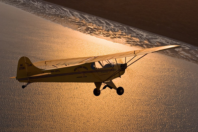 """Claudia's Cub"", VH-UYL, approaches French Island on Western Port Bay, Victoria as the sun rises. Straight out of the Piper Cub sales brochure. J2 Cub owned by Claudia and Brian Jones and Rob Black. Pilot Brian Jones."