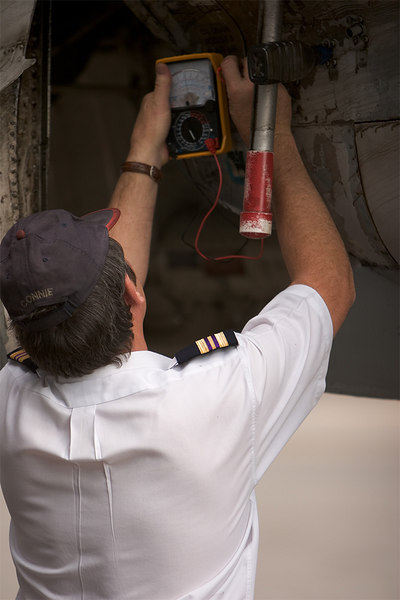 Joe checks for chips. Discontunity on the meter shows that there are no metal chips collecting on the magnetic plug in each engine. Red plug protects his shirt from oil drips.