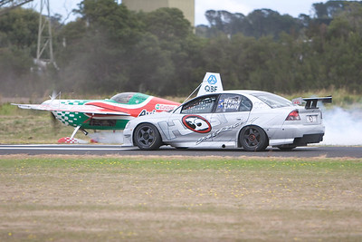 "Pip Borrman's Castrol Aviator Edge 540 momentarily out-dragged Todd Kelly's V8 Supercar ""thrill ride"" Commodore. The car beat the aircraft in the first match race but Borrman challenged the Bathurst 1000 winner to a second duel and justice was done!  When Todd had to brake at the end of runway 17, Pip flung the Edge 540 skywards. A thumb-the-nose sort of gesture... ""You might have beaten me to the end of the strip but look what I can do."""