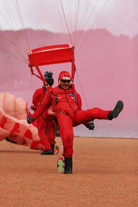 "R.D. Smith, a member of the Australian Army Red Berets Parachute Display team making an eventful landing  on the parade ground beside Lake Burley Griffin in Canberra during the VP Day celebrations on Saturday 13th September 2005. Only the most skilful can clown around! Pink smoke is from the wind-direction smoke canister.<br /> <br /> Awarded ""Merit"" and ""Top Shot"" at Pennant Hills Photographic Club when presented as a black and white image. Judged by Yvonne Lewington."