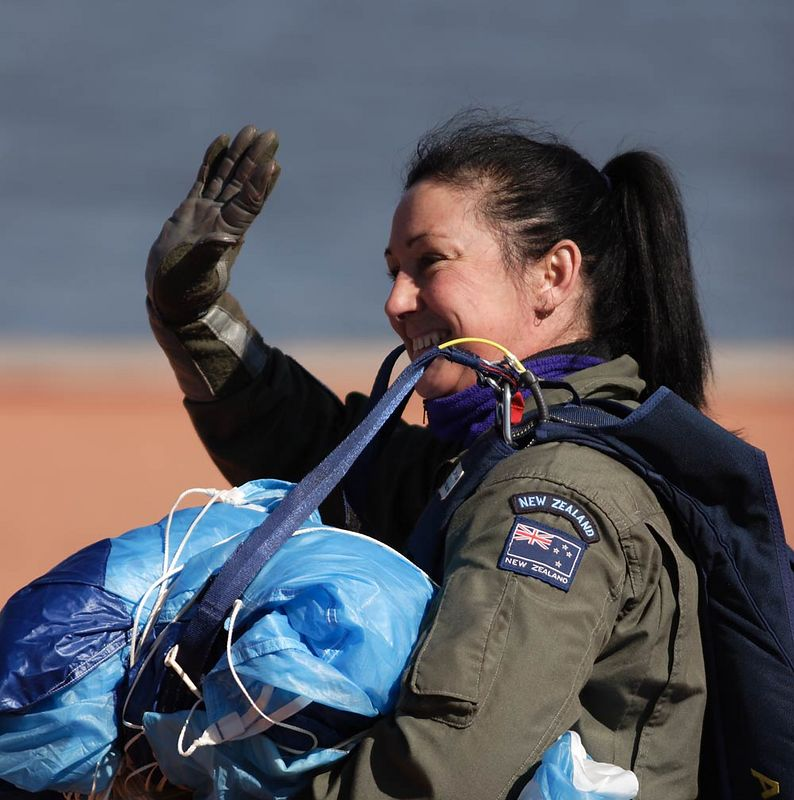 Female member of the  RNZAF Kiwi Blue Parachute Team acknowledges the accolades of the enthusiastic veterans.