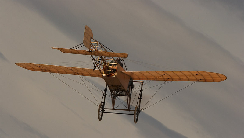 Blériot XI, built in 1919, in a climbing turn against a striated sky.