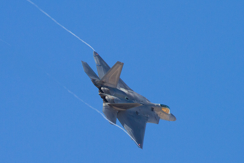 An F-22 banking after taking off from Nellis AFB.