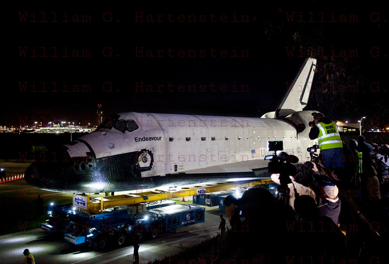 OV-105 Endeavour departs LAX on Northside Parkway then turns up McConnell Ave.with LAX Control Tower in background Oct. 13, 2012