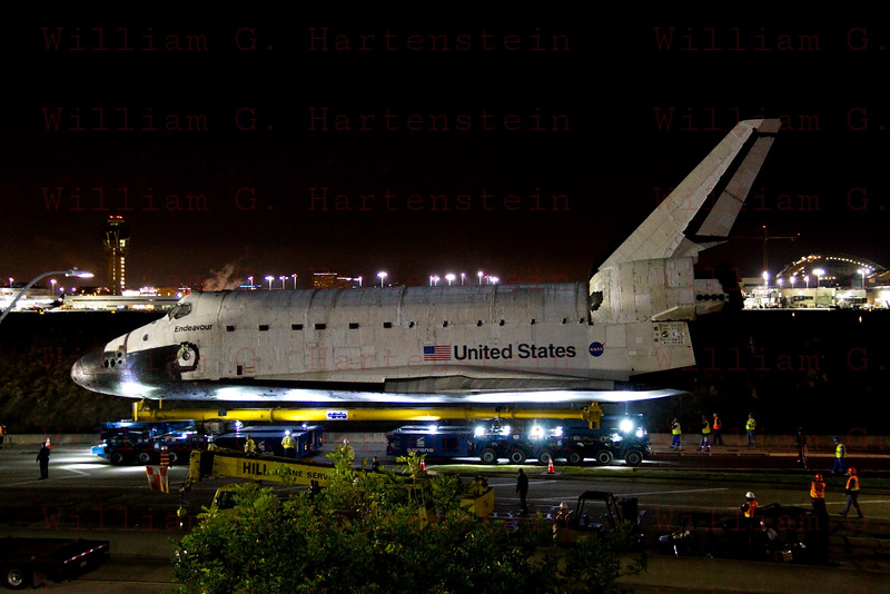 OV-105 Endeavour departs LAX on Northside Parkway with LAX Control Tower in background Oct. 13, 2012