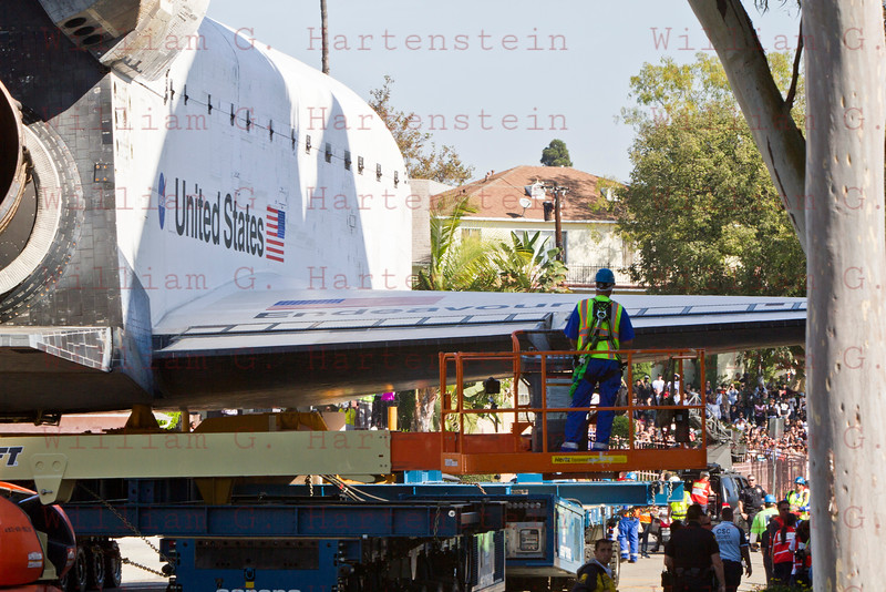 Worker checks clearence as OV-105 Endeavour heads up Crenshaw Dr. in Inglewood, CA. Oct. 13, 2012
