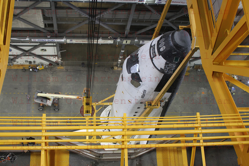 CAPE CANAVERAL, Fla. -- In Vehicle Assembly Building at NASA's Kennedy Space Center in Florida, an overhead crane suspends shuttle Atlantis above the transfer aisle. The spacecraft will be moved into a high bay where it will be lowered and attached to its external fuel tank and solid rocket boosters already on the mobile launcher platform. Commander Chris Ferguson, Pilot Doug Hurley and Mission Specialists Sandra Magnus and Rex Walheim are expected to launch in mid-July, taking with them the Raffaello multi-purpose logistics module packed with supplies, logistics and spare parts.