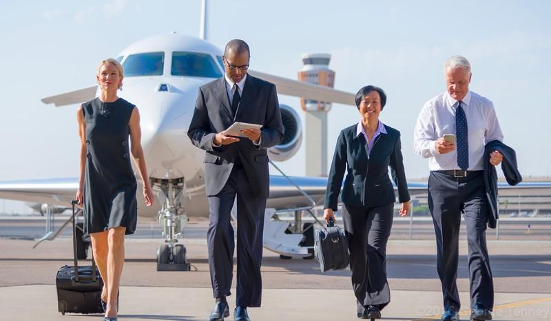 Business travelers deplaning Dassault Falcon 7x  business jet parked on hangar ramp. Honeywell Flight Operations, Phoenix, AZ. GoDirect, HAPP, MPP.