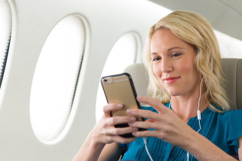 Business jet passenger with headphones and smartphone in Dassault Falcon 7x cabin. Honeywell Flight Operations, Phoenix, AZ. GoDirect, HAPP, MPP.