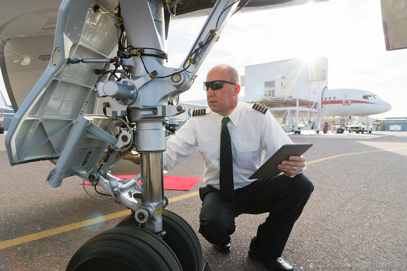 Pilot doing preflight check with tablet on Dassault Falcon 7x business jet. Jeff Bender. Honeywell Flight Operations, Phoenix, Arizona. GoDirect, HAPP, MPP.