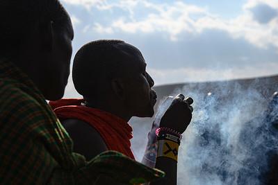 Maasai tribesman starts a fire after rubbing sticks together