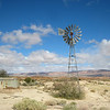 A common scene in the desert - a wind operated water pump and holding tank to supply livestock.<br /> Going north through the desert from Pofadder to the Namibian border.<br /> Aug. 19, 2009<br /> ©Peter Candido All Rights Reserved