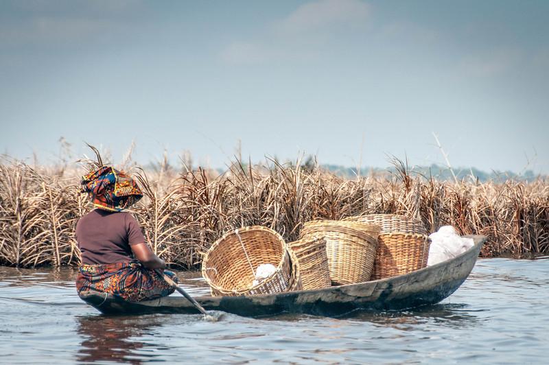 Woman rowing a boat in Cotonou, Benin