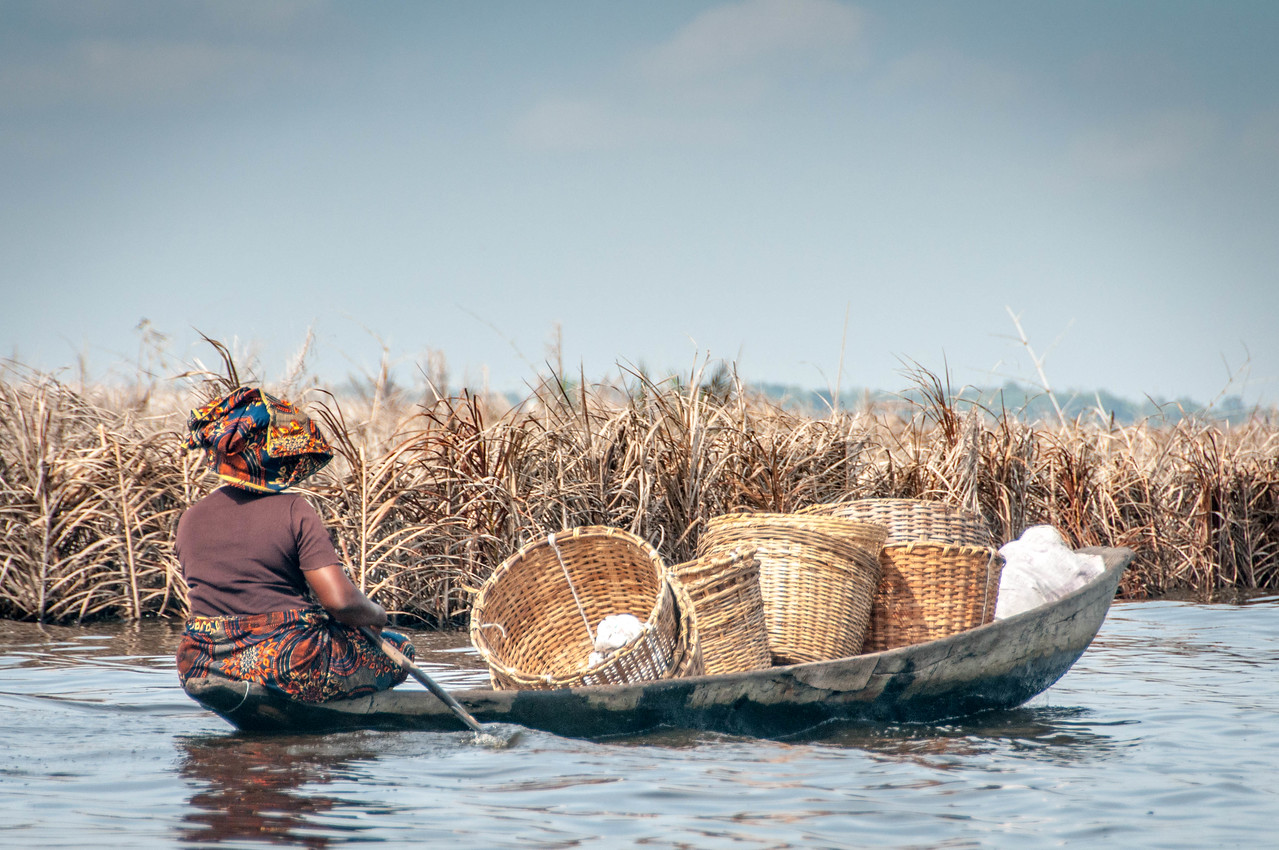 Woman rowing a boat in Cotonou, Benin