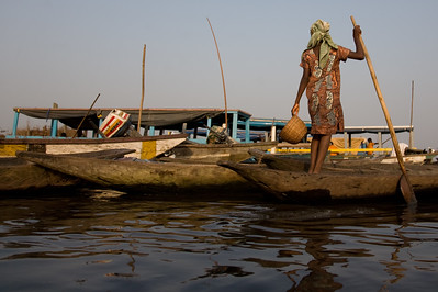 GANVIE, BENIN - DECEMBER, 2006: Woman stands up in a small canoe. The fishing town of Ganvie built completely on stilts and accessable only by water.27,000 villagers live here in bamboo huts on Lake Nokoue near Cotonou. ( Photo by: Christopher Herwig )