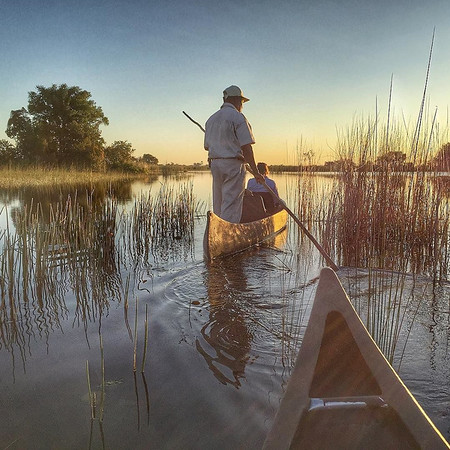 """Delta"" John Carter, a local legend for his knowledge and wisdom drawn from growing up in a village along the Okavango Delta. He served as one of our guides, including on this late afternoon paddle along the slowly rising network of waterways just outside Camp Okavango. A remarkable experience all its own, but astonishing when you consider the ecology and cycle that sees the annual filling of these channels, then absorption of the water into the sands of the Kalahari Desert. In the current season, in only a few days, once dry patches turn to lagoon as the flood waters arrive. It gave us a sense of what the same land looks like flush with water…and without. via Instagram http://ift.tt/1Qdq1sS"