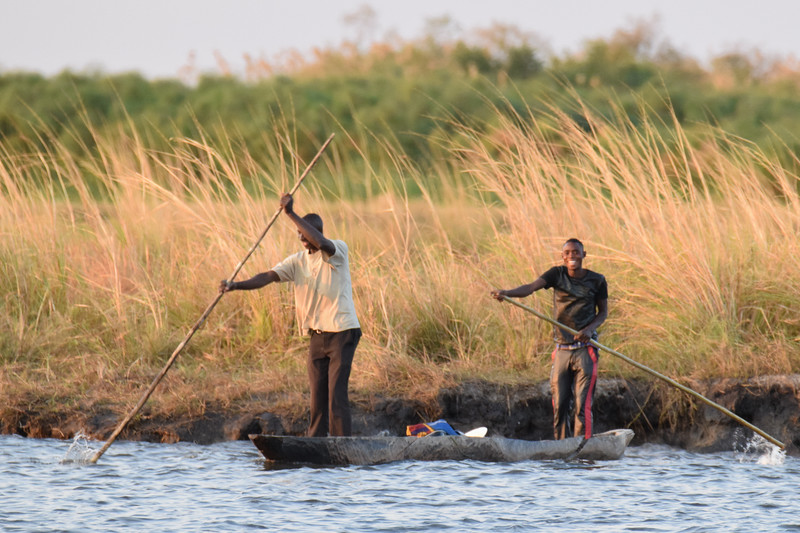 Men crossing a Chobe River in the traditional Mokoro boat