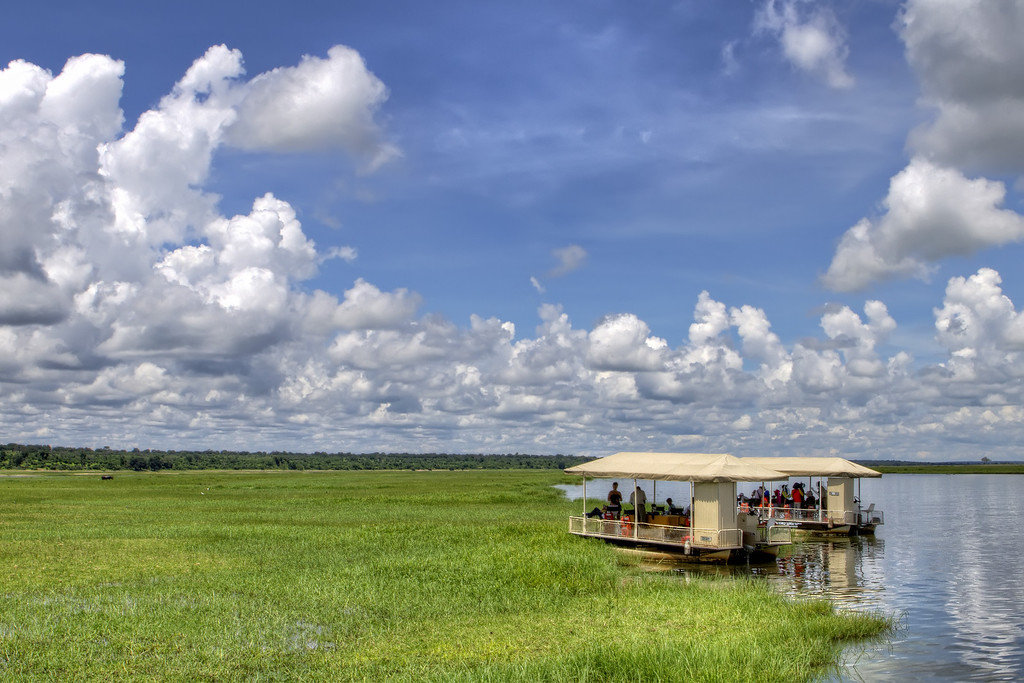Light fluffy clouds in a blue sky over the green grasses of Botswana with a safari boat moored on the river.