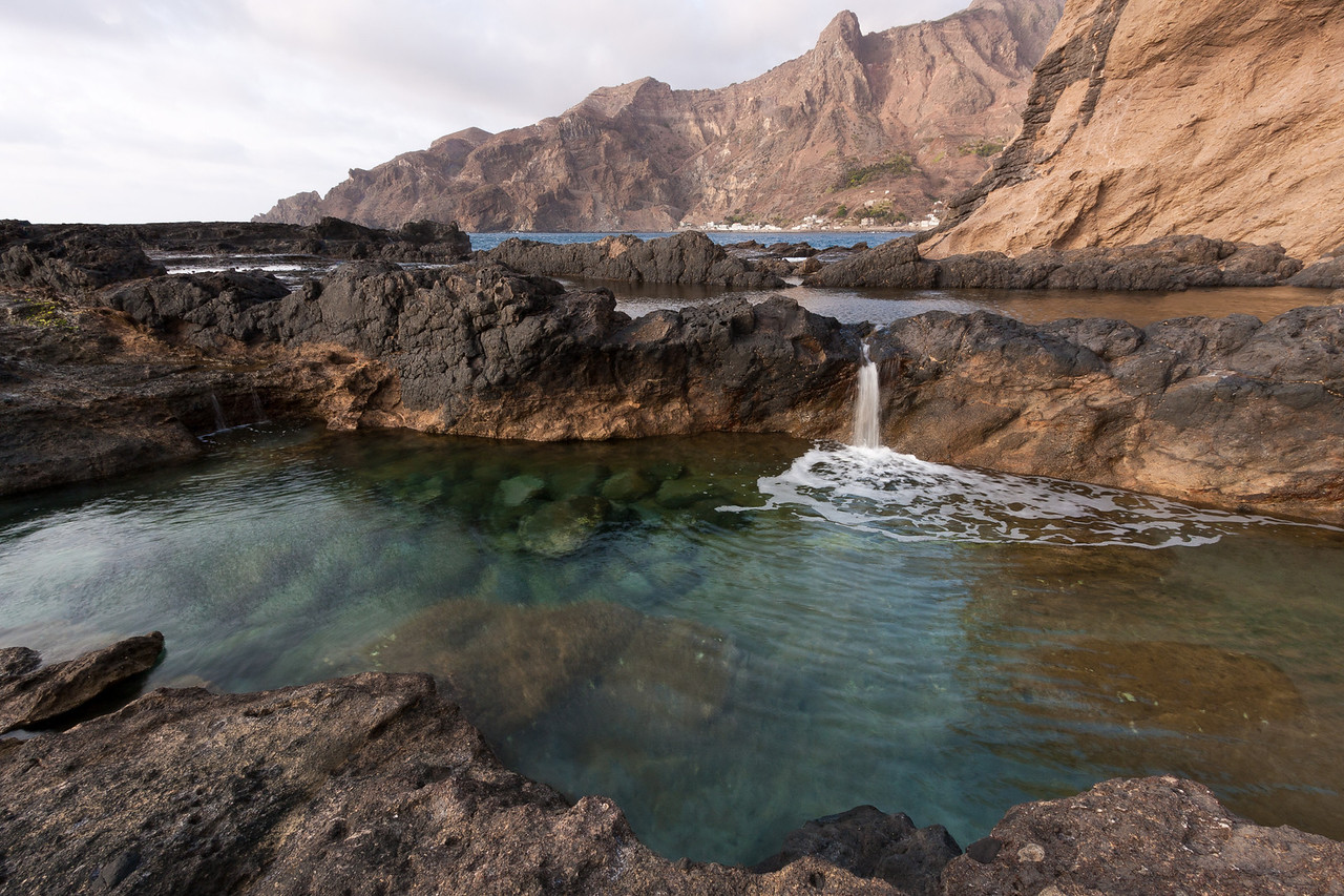 Tidal pools and a small village sit below the island's ubiquitous barren cliffs.<br /> <br /> Location: Fajã d' Ãgua village, Brava island, Cape Verde<br /> <br /> Lens used: Canon 10-22mm f3.5-4.5