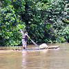 Village lady paddling downstream with a fishing net piled in the front of her canoe. Dzangha River, Central African Republic