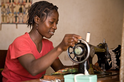 Young Liberian woman learning how to sew