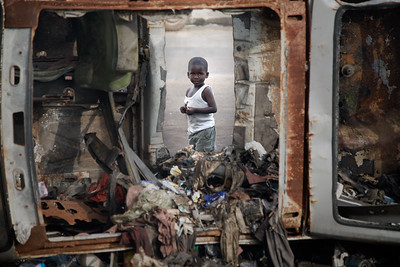 Young boy looks through hole in garbage dump