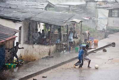 ARKIV 060903 - Children playing football in the rain on Gurley Street. Monrovia, Liberia Foto: Christopher Herwig - Kod 9266