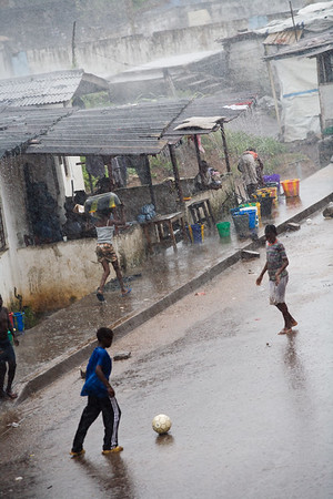 MONROVIA, LIBERIA - SEPTEMBER, 2006:  Children playing football in the rain on Gurley Street. (Photo by: Christopher Herwig)