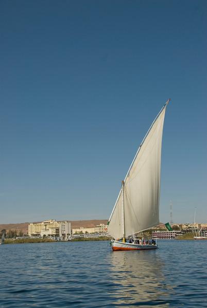 Felucca on Nile River against city skyline - Aswan, Egypt